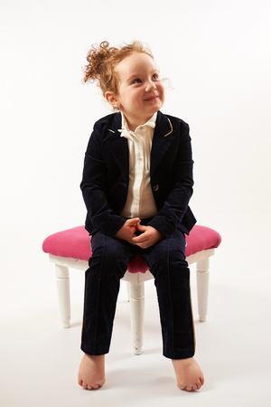 pouting: Little girl in black suit sitting on a rose stool and pouting