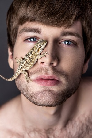 Portrait of a Young Handsome Man with Lizard on His Face Stock Photo