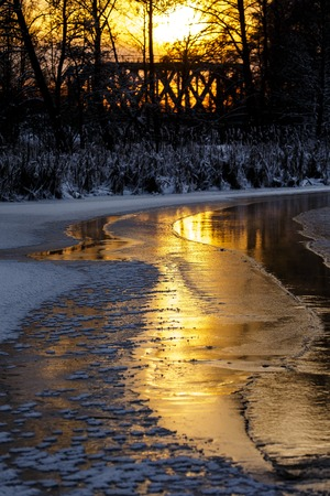 Colorful evening with golden reflection on the winter river