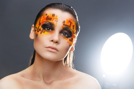 subculture: Portrait of a girl with an original make-up. Beauty close-up with orange and red rhinestones on a face of the model