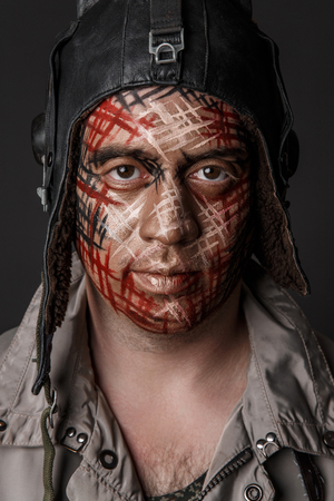 comedian: Portrait of Brutal Man with Creative Military Style Camouflage. Face Paint.  Close up on black background