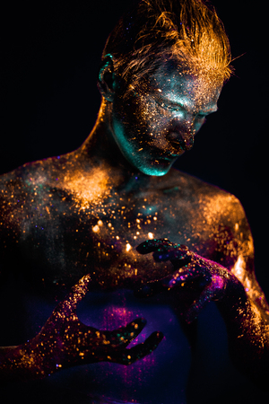 Conceptual shot of light and shine fluorescent  colors young mans face 版權商用圖片