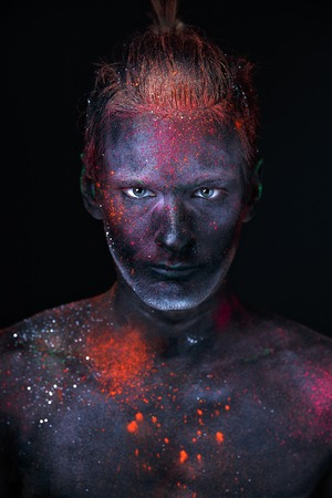 Conceptual shot of light and shine fluorescent  colors young mans face Stock Photo