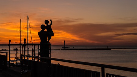 Silhouettes of mother and child against the background of the rising sun in the seaport Stock Photo