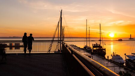 Romantic couple meets the dawn in the seaport