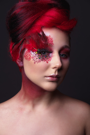Portrait of a beauty young  girl with red hair.  Creative ingenious makeup with feathers, rhinestones and large eyelashes Stock Photo