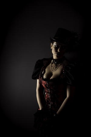 Emotional Portrait of Young Woman in Steampunk or Retro style. Studio shot. Model on a Black Background