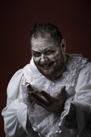 Portrait of a Scary Evil Clown.  Studio shot with horrible face art Reklamní fotografie - 115521718