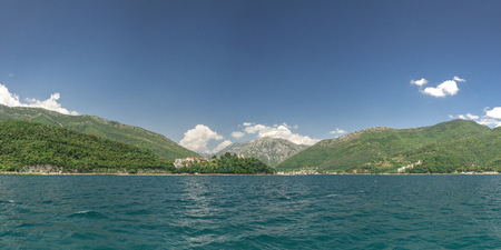 Panoramic view from the sea to the Kamenari-Lepetane Ferry crossing in the Bay of Kotor, Montenegro, in a sunny summer day.