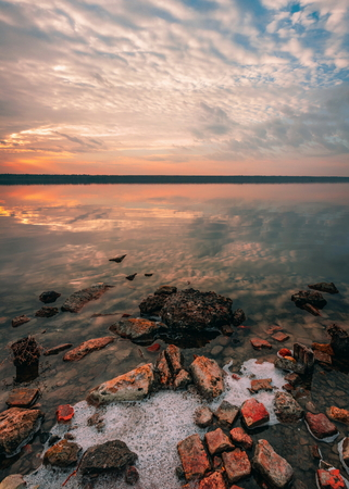 Stones on the lake in the red light of summer sunset Archivio Fotografico