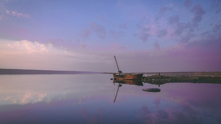 Panoramic view of the clouds above the water in a pink and purple sunset Archivio Fotografico
