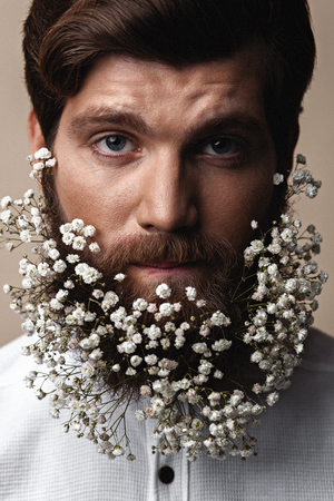 Creative Portrait of young beautiful man with a beard decorated with flowers. Banco de Imagens