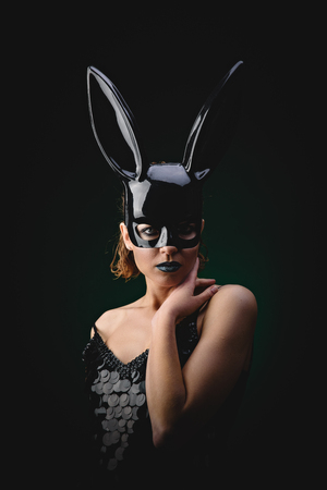 Sexy woman with a Easter bunny black mask standing on a dark background and looks sensually
