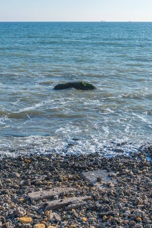 Lonely stone in the sea at the coast Imagens