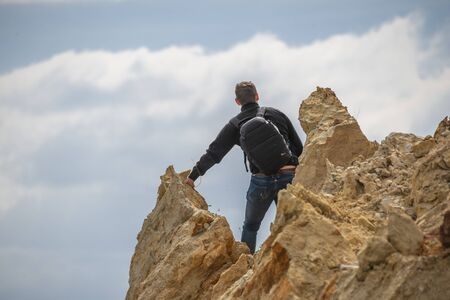 Grigoryevka, Ukraine - 05.09.2019 A tourist looks at the sky on a cliff from a shell rock A tourist looks at the sky on a cliff of a shell rock near the village of Grigoryevka in Ukraine 写真素材