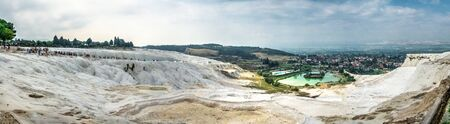 White mountain and green lake in Pamukkale. Panoramic view from above on a summer morning.
