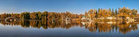 Autumn landscape with a lake and yellow trees in the village of Ivanki, Cherkasy region, Ukraine, on a sunny autumn evening 스톡 콘텐츠