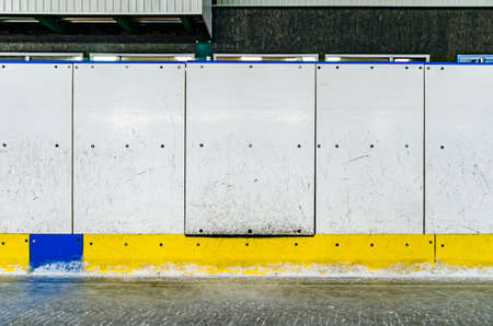 Hockey rink side boards with door and scratched and damaged surface