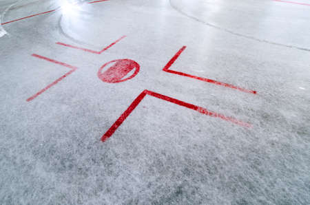 Hockey rink with faceoff spot on freshly resurfaced ice with marks of water