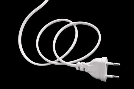 White plug with a wire on a black background 스톡 콘텐츠