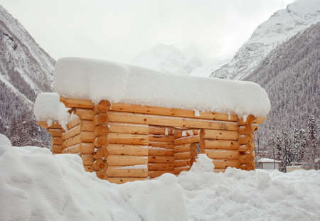 snowdrifts: unfinished log cabin among snowdrifts