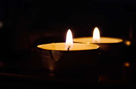 alight: Candle lights, flickering flame in the dark Stock Photo