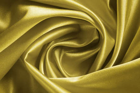 drape a golden satin fabric in the form of roses for the background Stock Photo