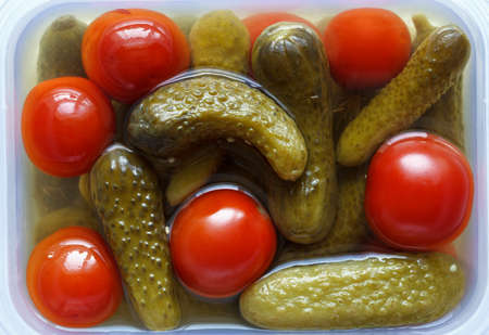 marinated gherkins: pickled gherkins cucumbers and cherry tomatoes in a container