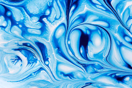 Abstract background of mixing  blue and white paints