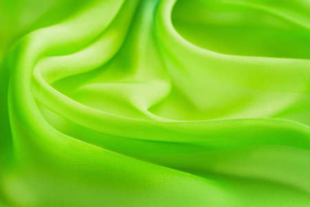 Abstract background folds bright yellow green transparent fabric