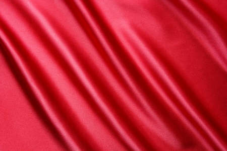 red satin fabric with large folds, as background Stock Photo