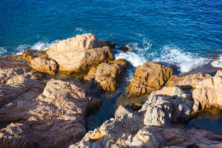 sea and coastal rocks illuminated by the setting sun in Spain, Catalonia