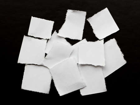 scraps of white paper on a black background