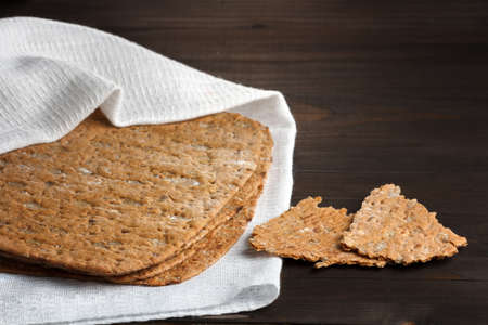 thin rye flour bread with bran and oat flakes on a white kitchen towel on table Stok Fotoğraf