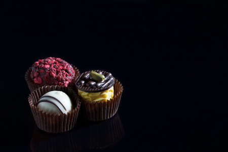 handmade chocolate candies on a black background with place for text
