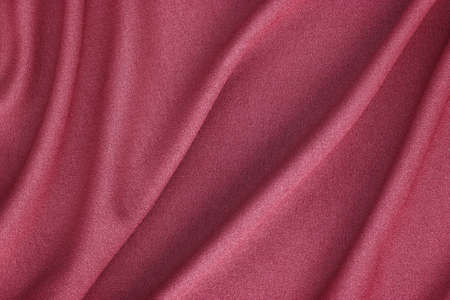 red synthetic fabric with large folds, textile background