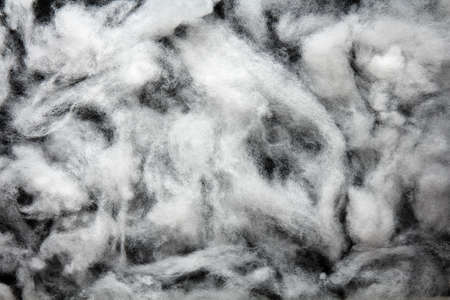 Siliconized hollowfiber, polyester fiber on a black background, used as a filler for blankets, pillows, clothes and upholstered furniture