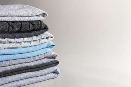 stack of folded knitted clothes on a gray background with place for text