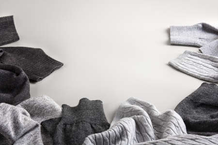 scattered knitted clothes on a gray background with place for text