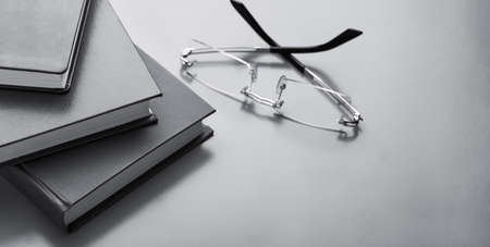 books and glasses on the table with place for text, monochrome