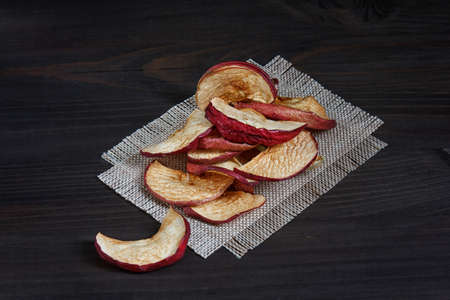 slices of dried apples on a dark wooden background Stock Photo