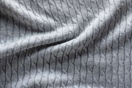 Knitted gray fabric with pigtail cable, texture with folds