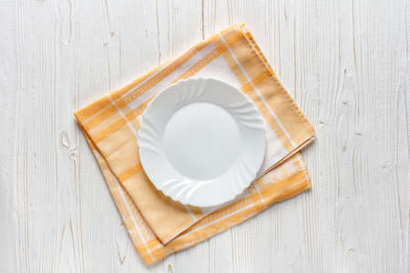 empty white plate on yellow kitchen towel, napkin on a wooden table, top view