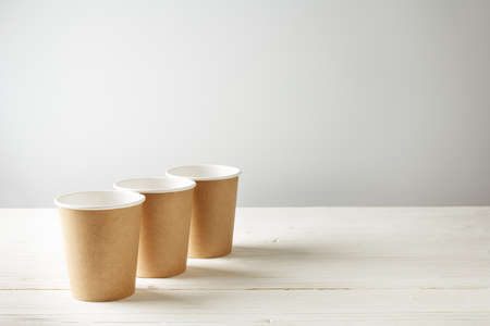 row of three paper cups on white wooden background with place for text 免版税图像