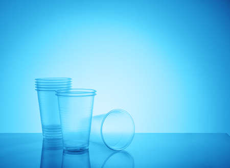 Empty disposable plastic cups on a blue
