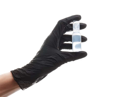 hand in a black nitrile glove holds a plastic medical ampoule with medicine, isolated on white