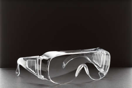 safety plastic transparent glasses on a black background with copy space