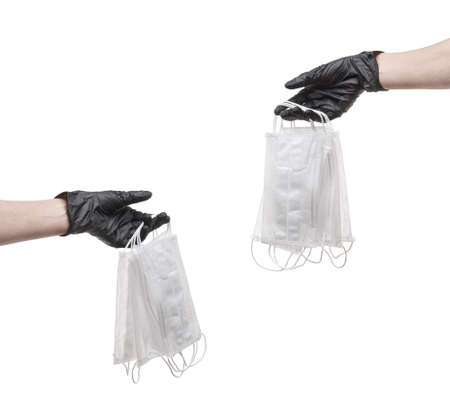 Hands in rubber  gloves pass medical masks isolated on white
