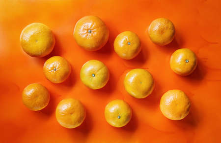 tangerines scattered on a bright orange background