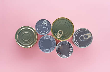 composition of  closed tin cans of different sizes on a pink background, top view